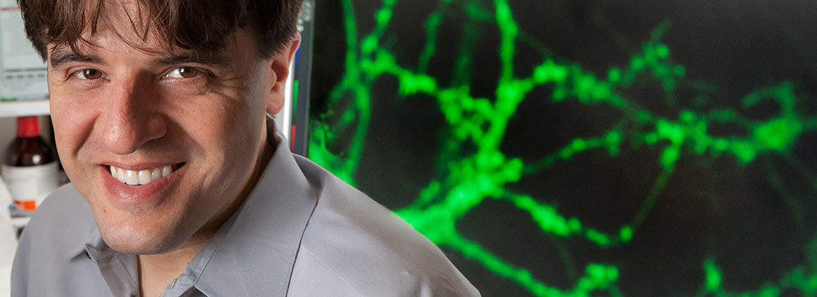 Karl Deisseroth in front of a sceen showing neurons