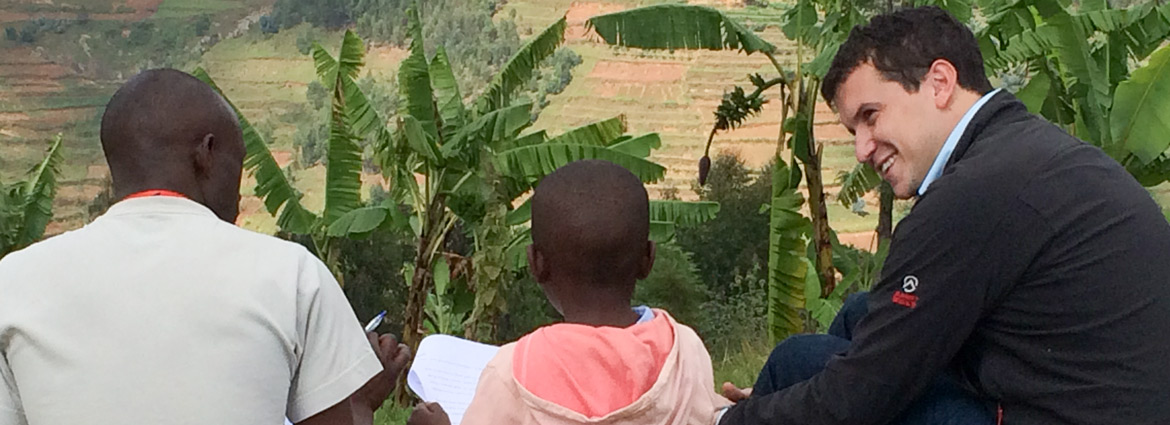 Stanford researcher Elliott Friedlander sitting on a hillside with a young Rwandan student and a reading proctor.